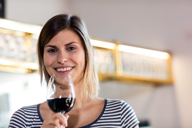 拿着葡萄酒杯的少妇在餐馆 库存图片