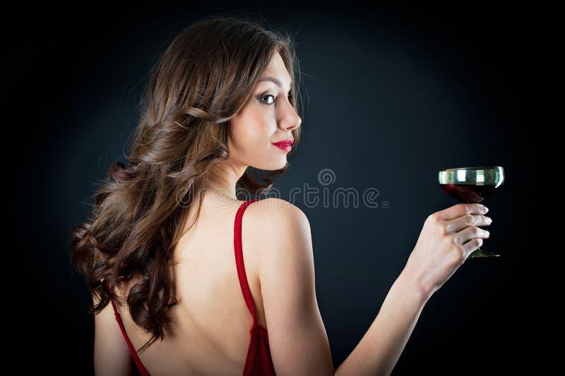 拿着葡萄酒杯的美丽的少妇剪影  图库摄影