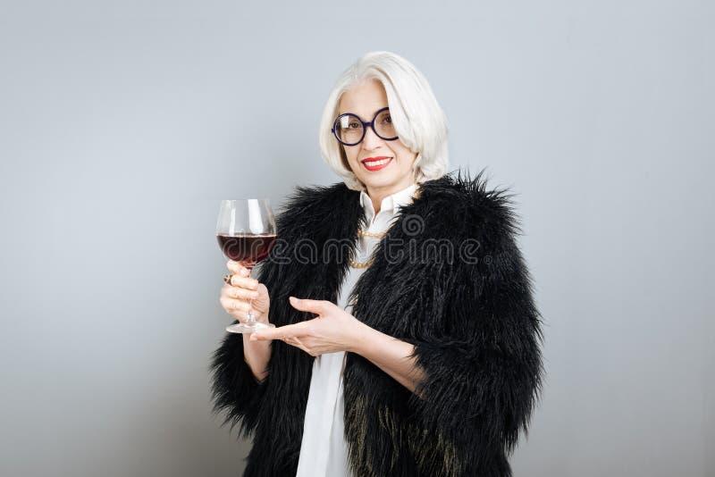 拿着葡萄酒杯的美丽的微笑的妇女 免版税库存图片