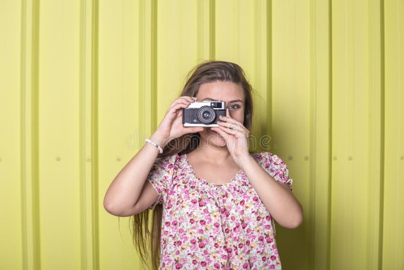 拿着葡萄酒照相机的美丽的妇女对黄色墙壁 库存图片