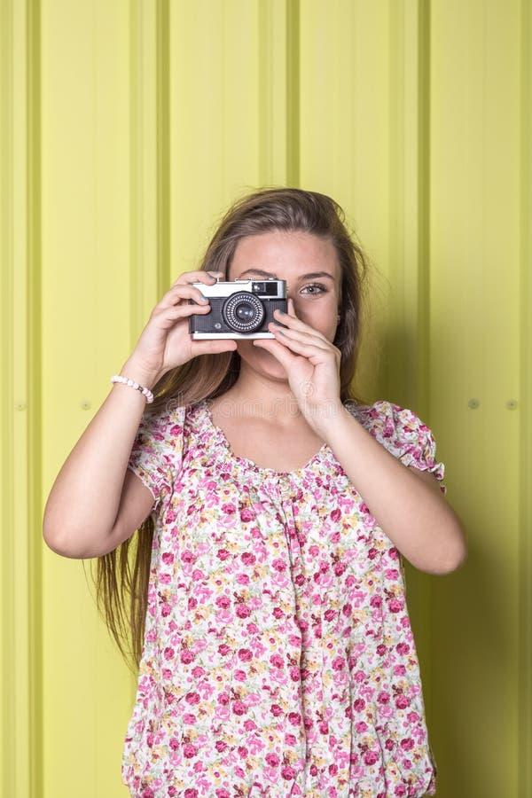 拿着葡萄酒照相机的美丽的妇女对黄色墙壁 免版税库存照片