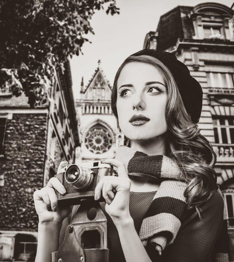 拿着葡萄酒照相机的贝雷帽和围巾的女孩 库存照片