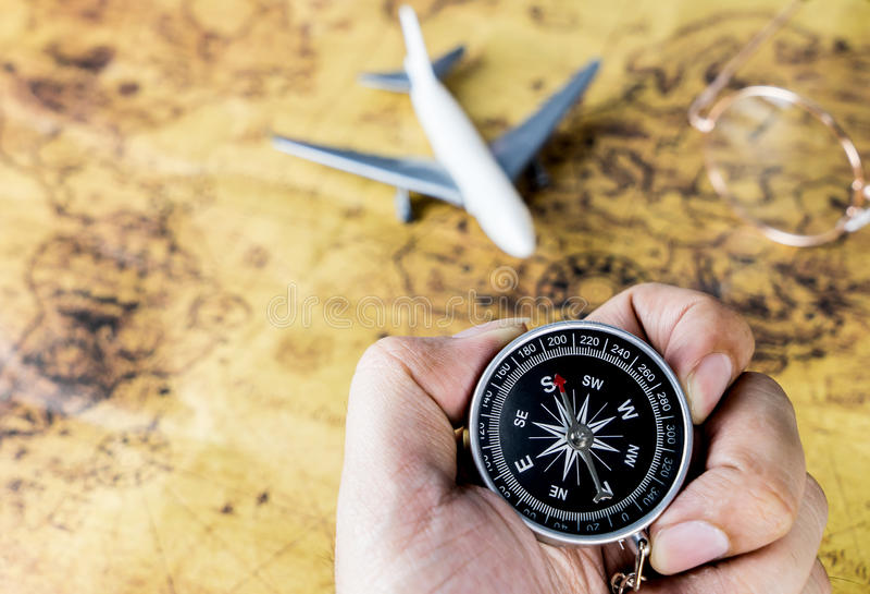 拿着葡萄酒航空旅行的手指南针 免版税库存照片