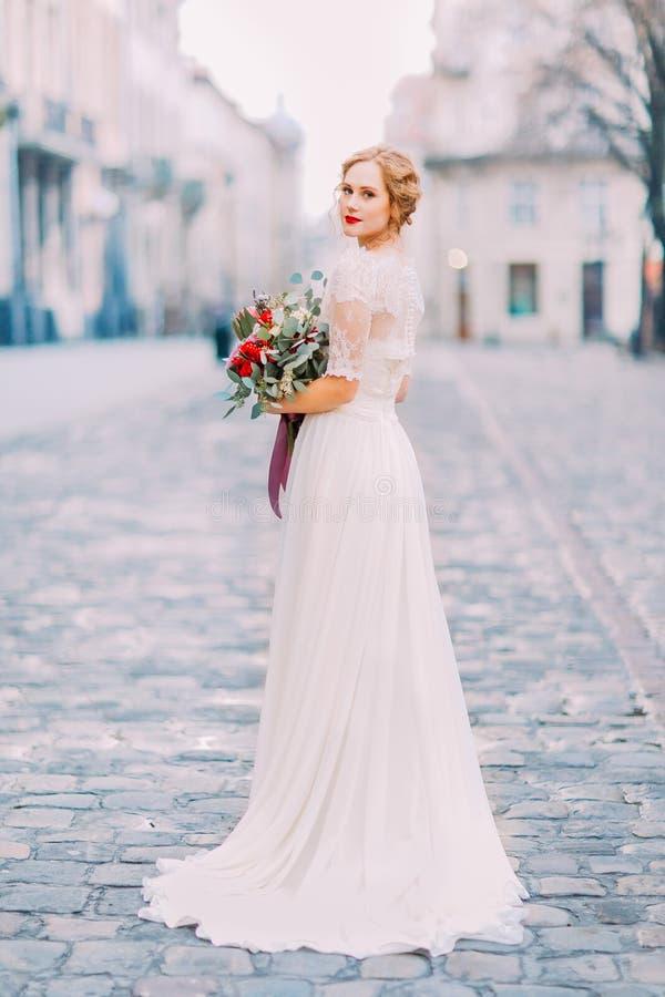 拿着葡萄酒花束的长的鞋带礼服的迷人的新娘看在肩膀入与老城市的照相机 免版税库存图片