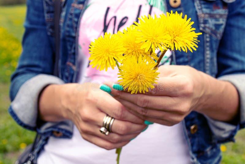 拿着蒲公英花束的年轻女人在绿色公园在春天 明亮和鲜花背景 库存照片