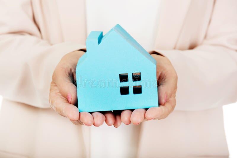 拿着蓝纸房子的年长女商人 免版税库存照片