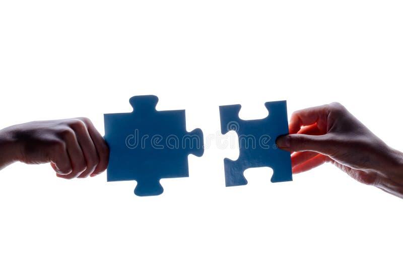 拿着蓝色七巧板片断的夫妇在白色背景的两手剪影  概念-连接想法,标志,标志, fr 免版税库存照片