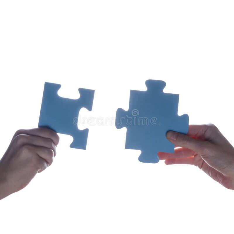 拿着蓝色七巧板片断的夫妇在白色背景的两手剪影  概念-连接想法,标志,标志, fr 免版税库存图片