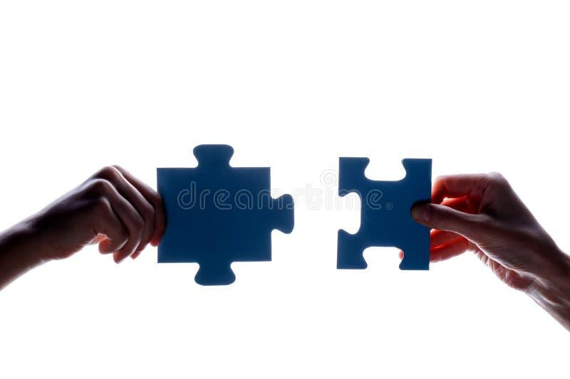 拿着蓝色七巧板片断的夫妇在白色背景的两手剪影  概念-连接想法,标志,标志, fr 库存图片