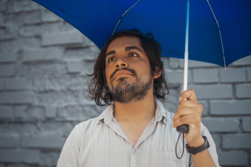 拿着蓝色伞的可爱的深色的拉丁人在灰色砖墙旁边 免版税库存图片