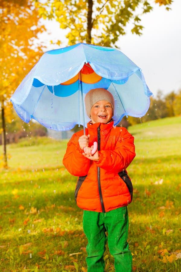 拿着蓝色伞的微笑的正面男孩在公园 免版税库存照片