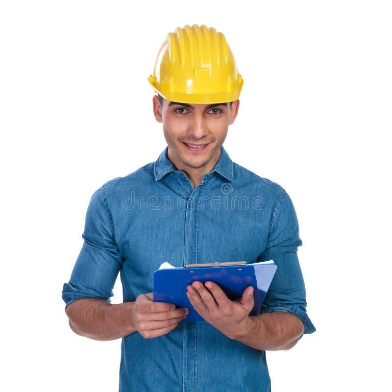 拿着蓝色剪贴板的英俊的工程师学生画象  图库摄影