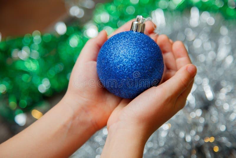 拿着蓝色圣诞节球的孩子 库存图片