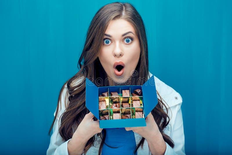 拿着蓝色框用巧克力糖的惊奇的妇女 免版税库存图片