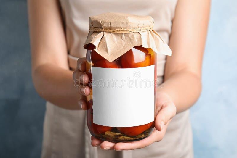 拿着蓝色背景空白贴纸的腌番茄玻璃罐的女子 免版税库存照片
