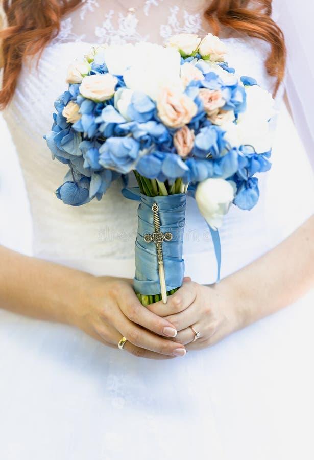 拿着蓝色花的新娘花束美丽的年轻新娘 免版税库存照片