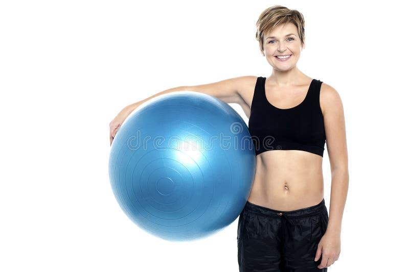 拿着蓝色pilates球的一个可爱的适应夫人 免版税图库摄影