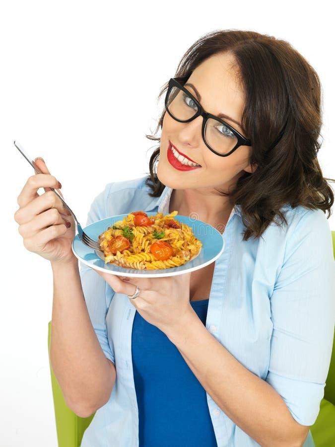 拿着蕃茄和蓬蒿Penne面团的板材美丽的愉快的年轻西班牙妇女 免版税库存图片