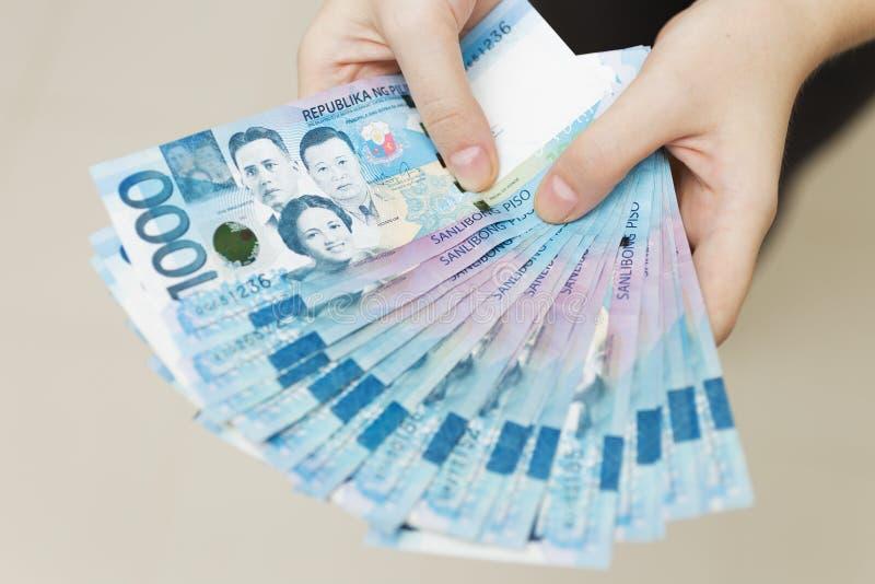 拿着薪金或付款捆绑一千个菲律宾比索现金的手,好象是富有的 炫耀,付帐或给brib 库存照片