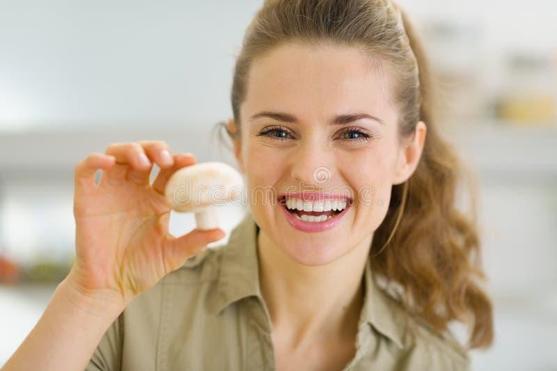 拿着蘑菇的愉快的年轻主妇在厨房里 免版税库存图片