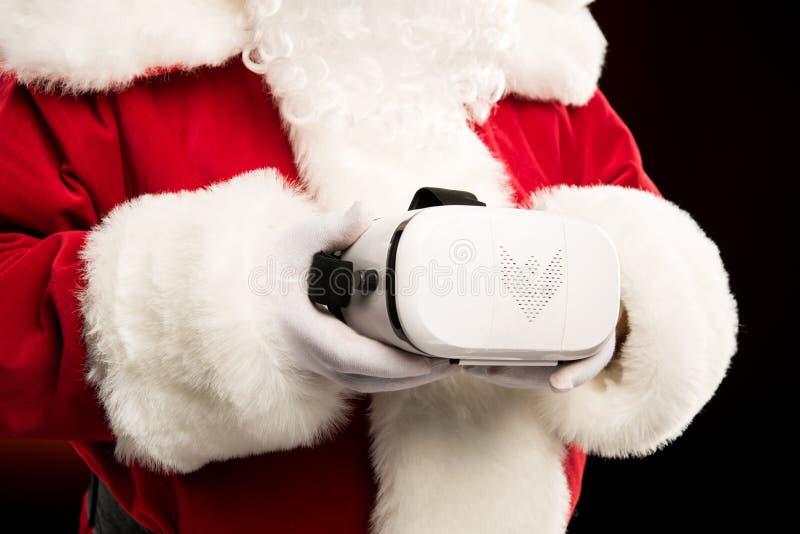 拿着虚拟现实耳机的圣诞老人播种的射击 免版税库存照片