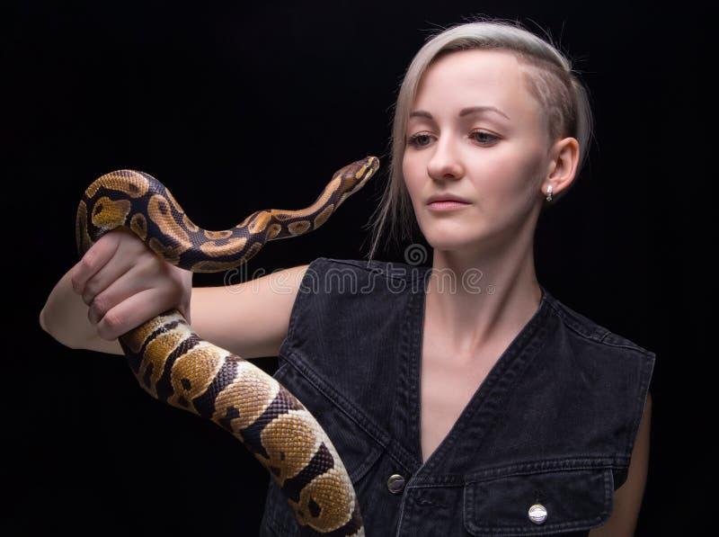 拿着蛇的白肤金发的妇女画象 图库摄影