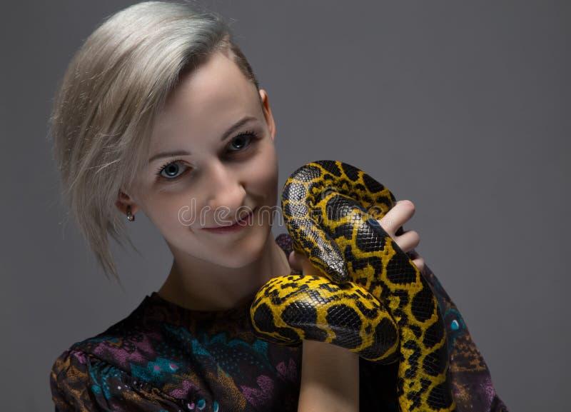 拿着蛇的白肤金发的微笑的妇女 库存照片