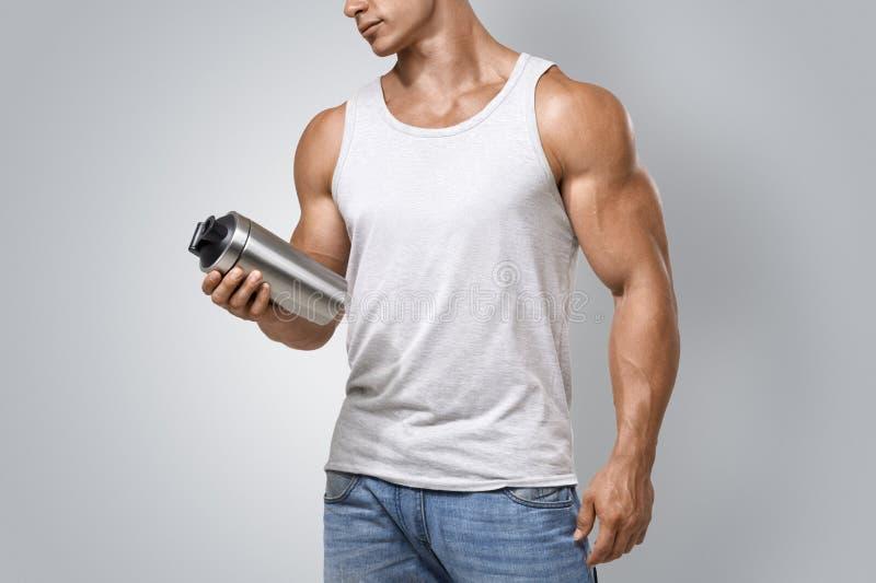 拿着蛋白质震动瓶的肌肉健身男性 免版税库存图片