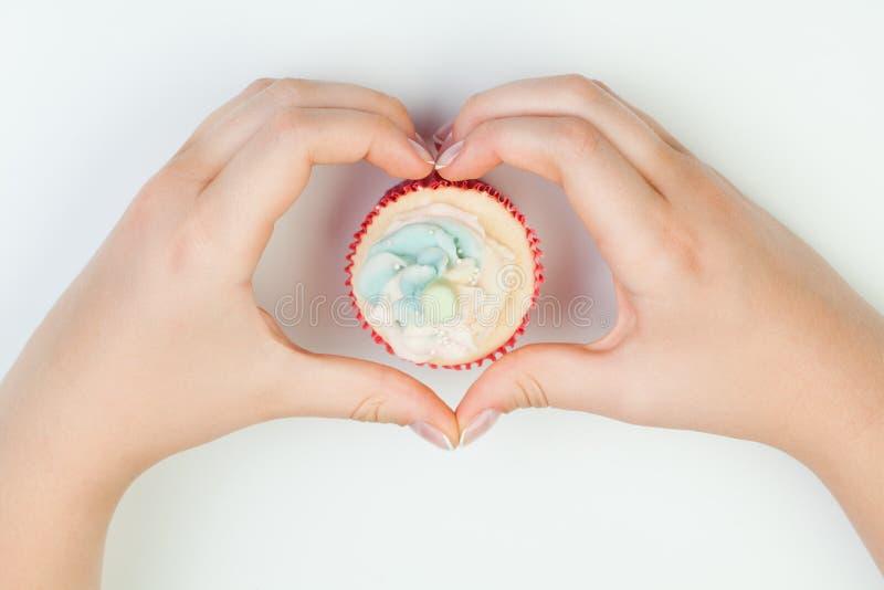 拿着蛋糕的美丽的被修剪的妇女的钉子 手在形状心脏 图库摄影