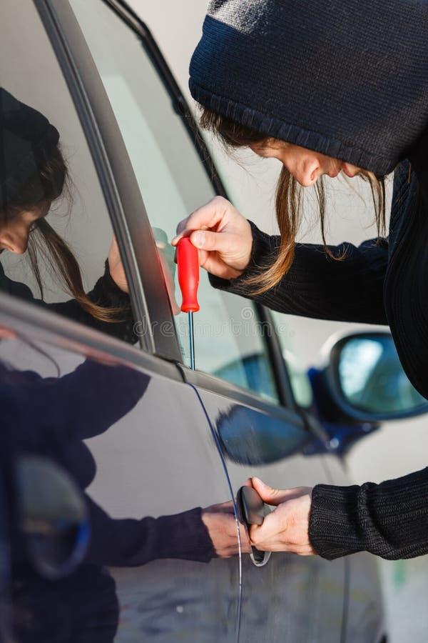 拿着螺丝刀的窃贼人闯进汽车 库存图片