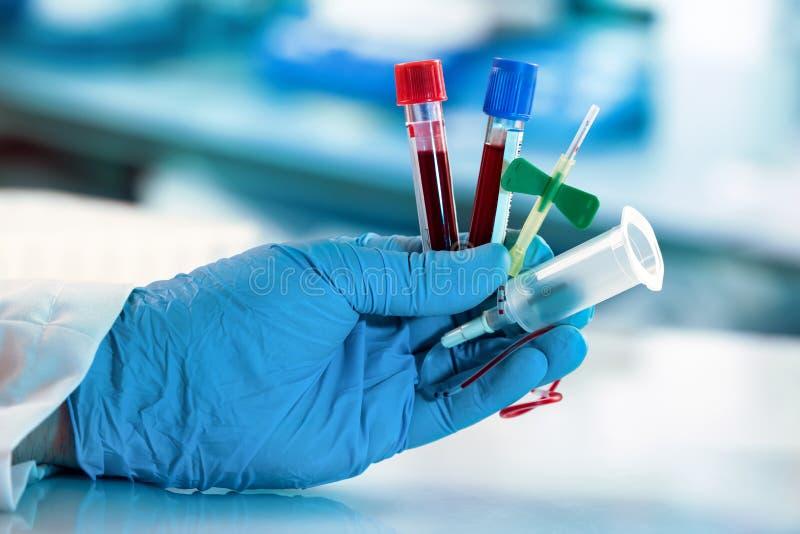 拿着血液汇集管和导尿管的化验员手 图库摄影