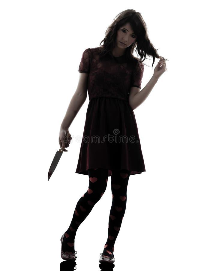 拿着血淋淋的刀子剪影的奇怪的少妇凶手 图库摄影