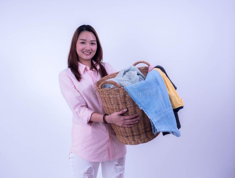 拿着衣物篮子的美丽的年轻主妇被隔绝在白色背景 拿着一个洗衣篮洗涤 疲乏 免版税库存图片