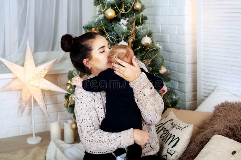 拿着衬衣的雍愉快的母亲婴儿男婴在圣诞树附近 愉快的育儿概念 有儿子的快乐的妈妈 免版税库存图片