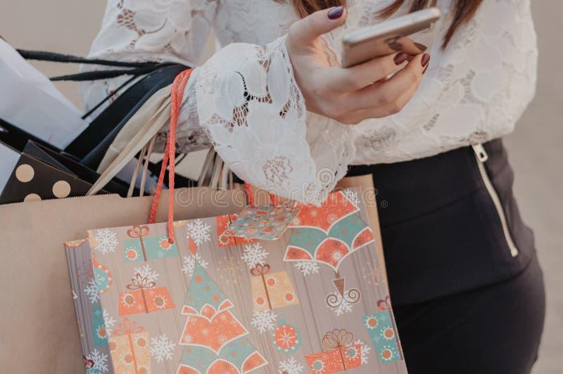 拿着袋子和手机的妇女在购物以后 免版税库存图片