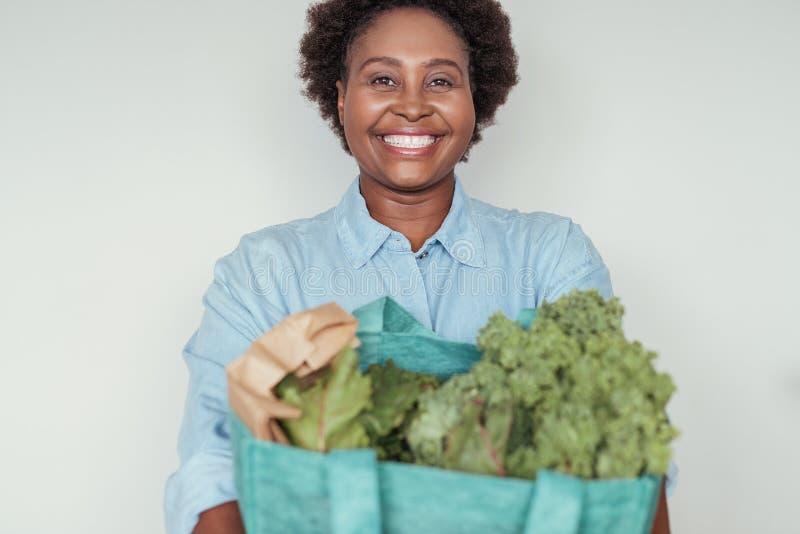 拿着袋子杂货的微笑的年轻非洲妇女 免版税库存照片
