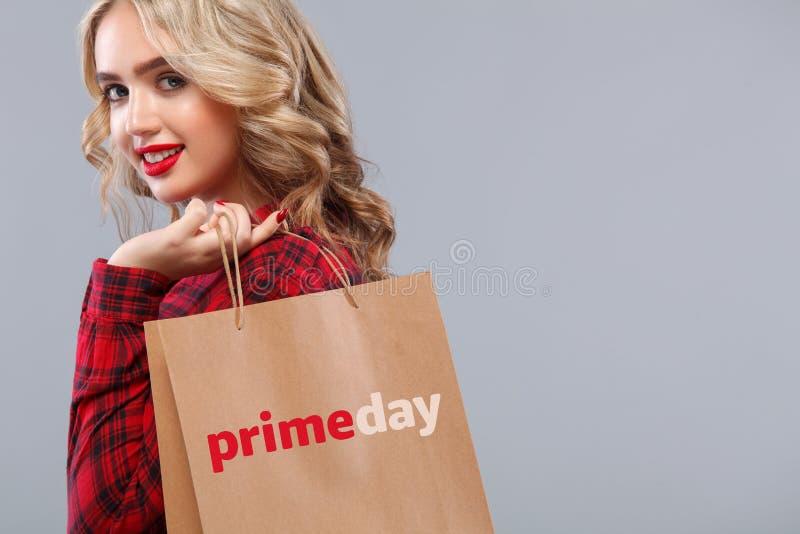 拿着袋子的购物的白肤金发的妇女被隔绝在灰色背景在黑星期五或头等天假日 PrimeDay 2018年 库存图片