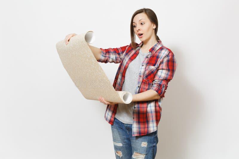 拿着被展开的墙纸卷的便服的年轻有关美女被隔绝在白色背景 免版税图库摄影