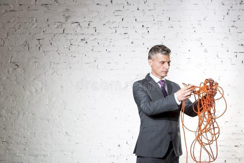 拿着被缠结的红色缆绳的确信的成熟商人对白色砖墙 免版税库存图片