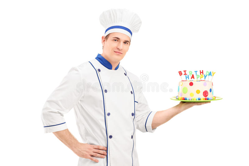 拿着装饰的生日蛋糕的制服的年轻男性厨师 库存照片