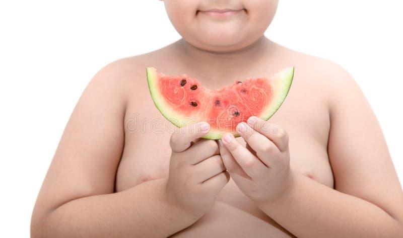 拿着西瓜的愉快的肥胖病男孩 图库摄影