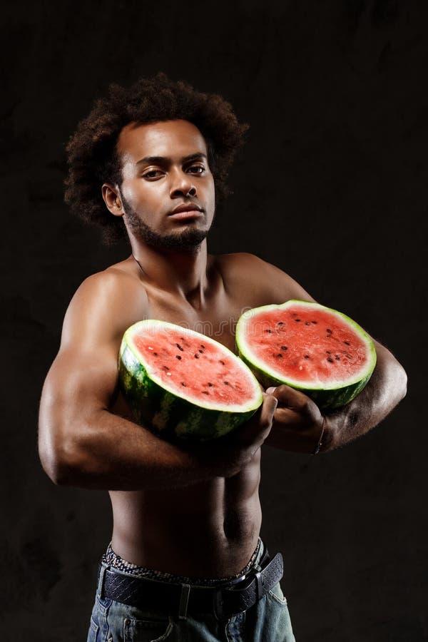 拿着西瓜的年轻嬉戏非洲人,摆在黑背景 图库摄影