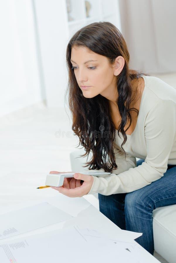 拿着计算器的夫人看起来压下 免版税图库摄影