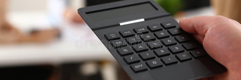 拿着计算器的男性手在办公室 免版税库存照片