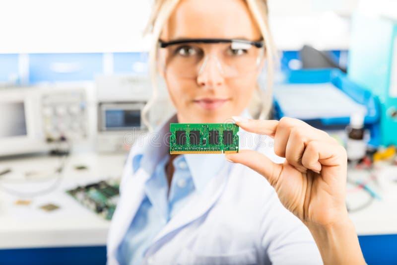 拿着记忆模块的年轻女性电子工程师手中 图库摄影