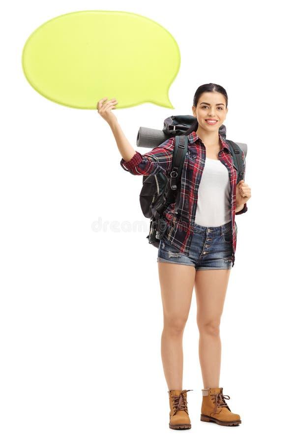 拿着讲话泡影的愉快的女性远足者 免版税图库摄影