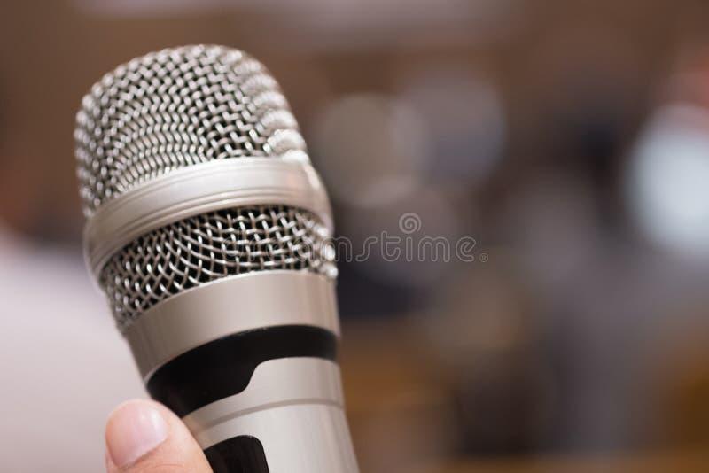 拿着讲话的手话筒在研究室 免版税库存图片