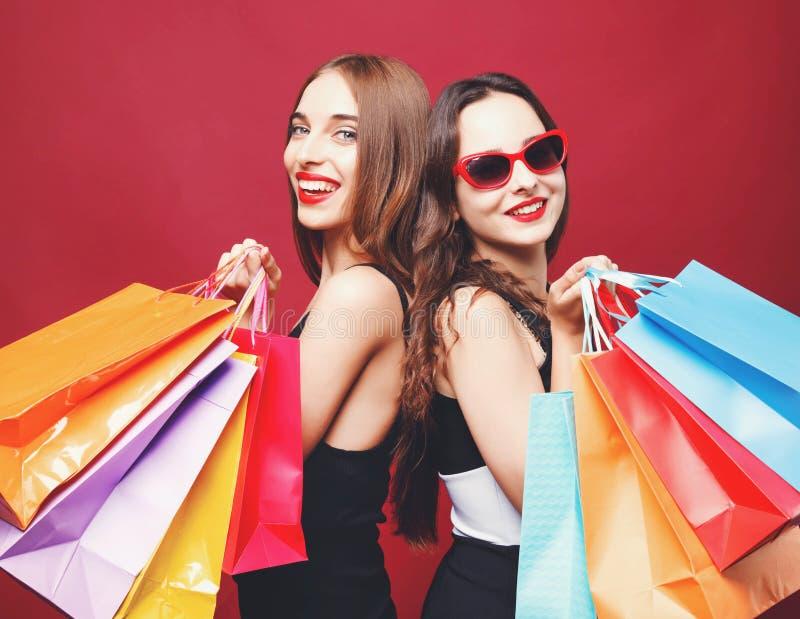 拿着许多五颜六色的纸购物袋的两个女朋友 库存图片
