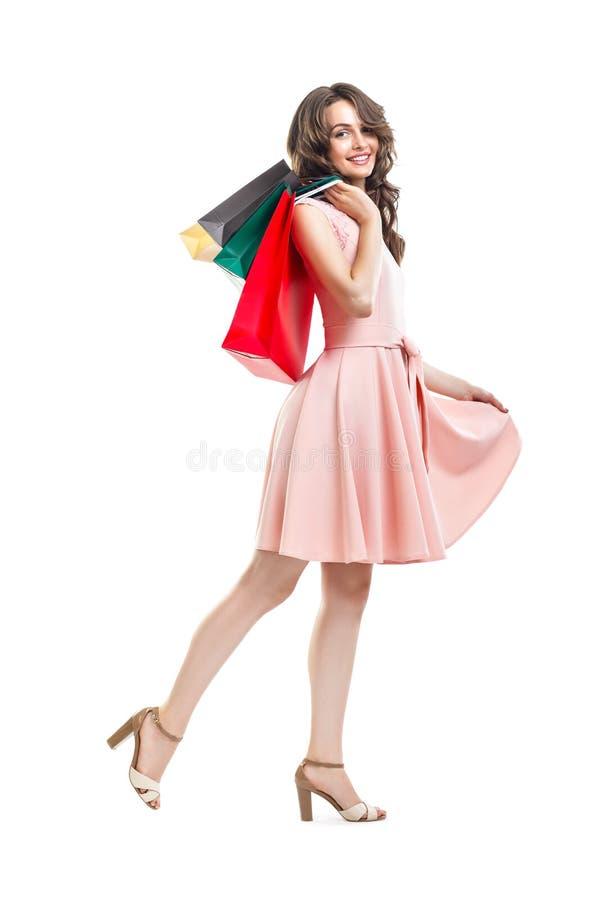 拿着许多五颜六色的购物袋isolat的愉快的美丽的妇女 免版税库存照片