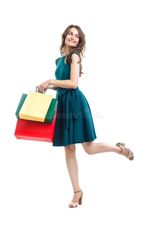 拿着许多五颜六色的购物袋isolat的愉快的美丽的妇女 图库摄影